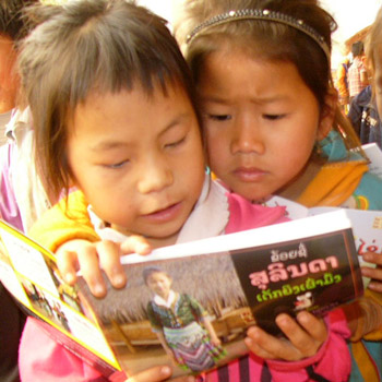 Two girls share a book about the Hmong ethnic group