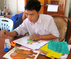 Tha Thao works on his next book, pictures of animals cut from paper.